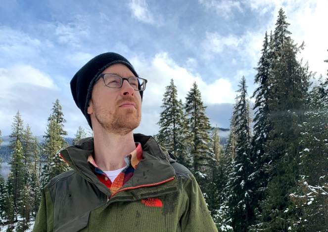 man in green jacket looking up at the sky, with snow covered pine trees in background