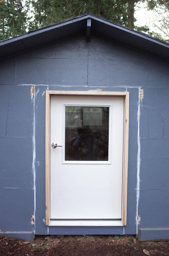 Front view of shed, with a new white door with glass window panel