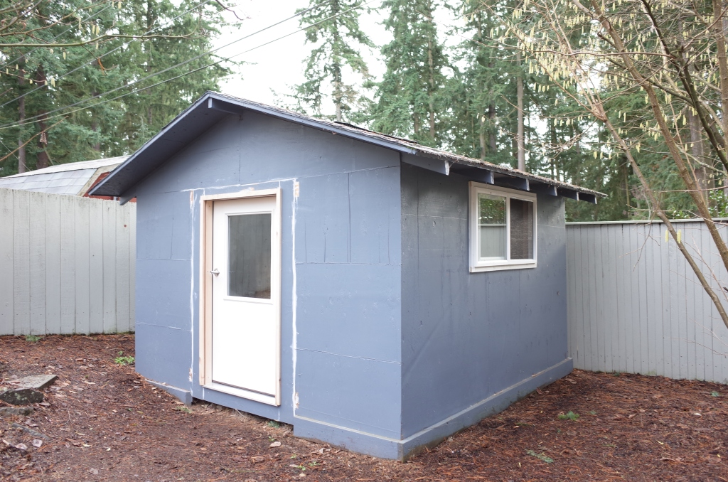 View of shed from outside, with new front door and side windows