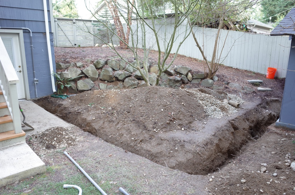 View of L-shaped trench dug in ground, surrounded by piles of dirt and stones