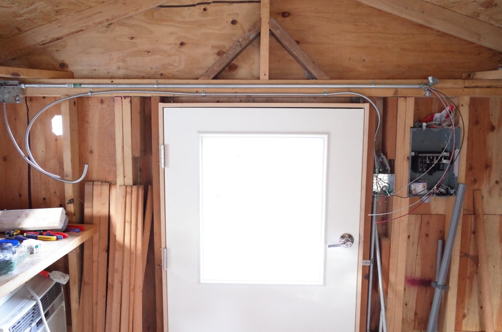 Inside shed front wall - electrical panel, conduit, and light switch