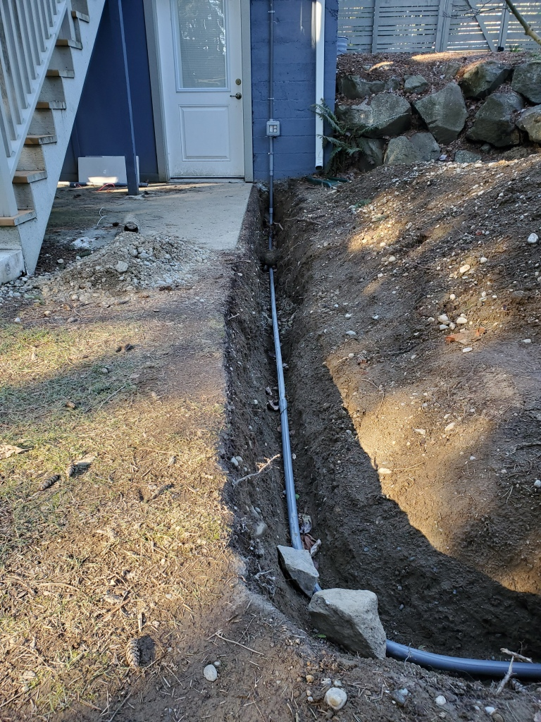 view of trench from house, with PVC pipe laid in trench