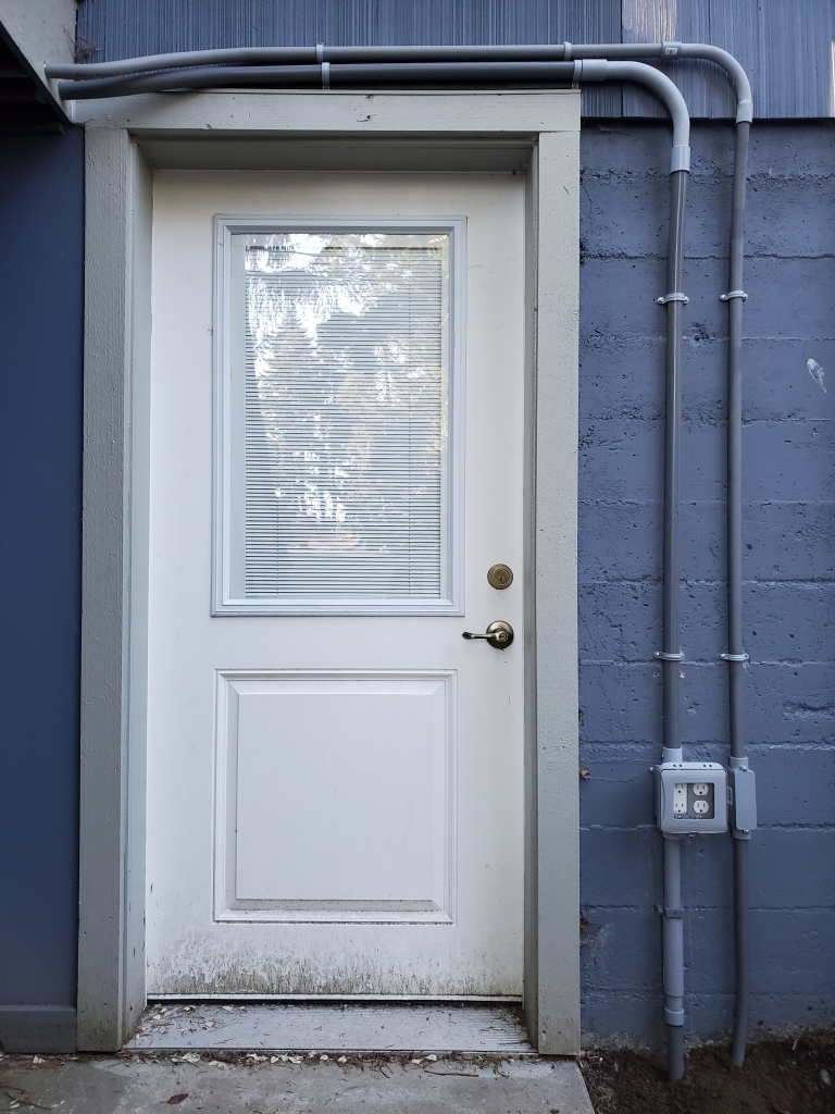 white door on blue exterior wall, with grey pvc conduit above and to the right of the door