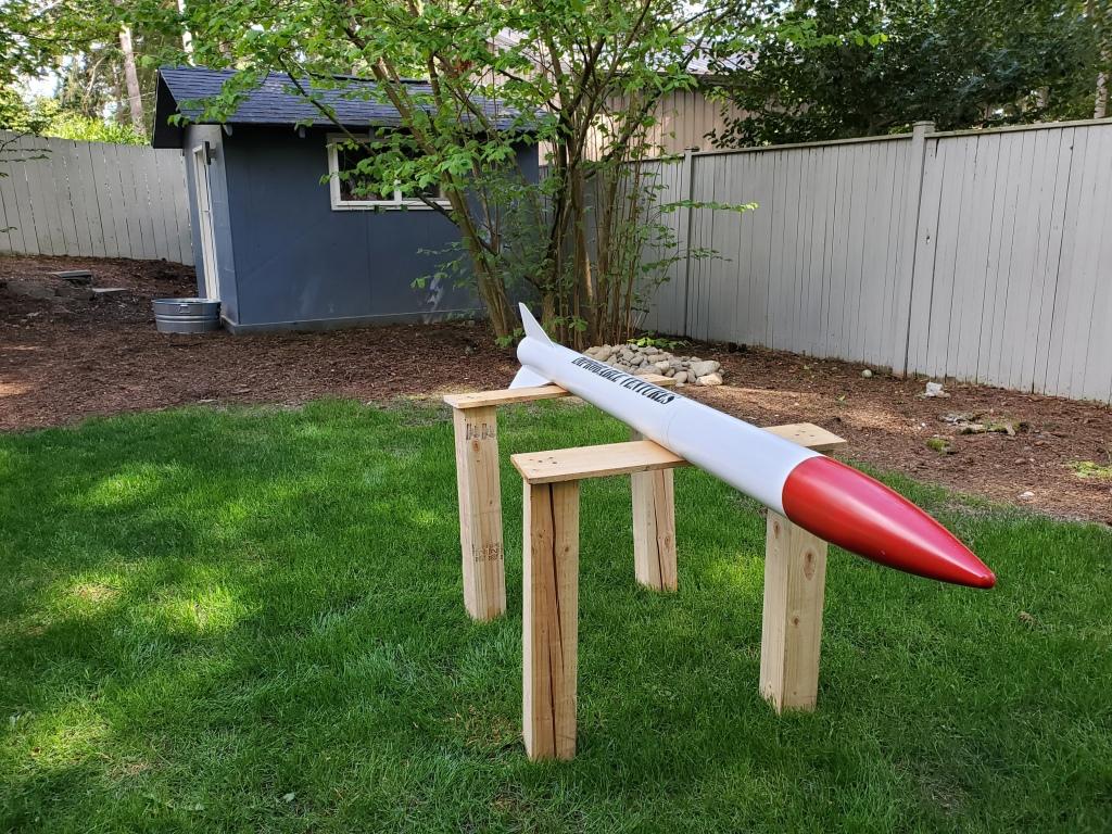HyperLOC 835 rocket on wooden test stand on green grass in yard