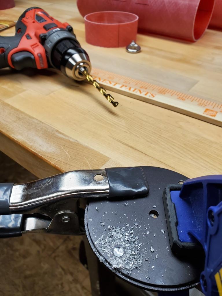 black circular aluminum bulk plate clamped to workbench with metal shavings