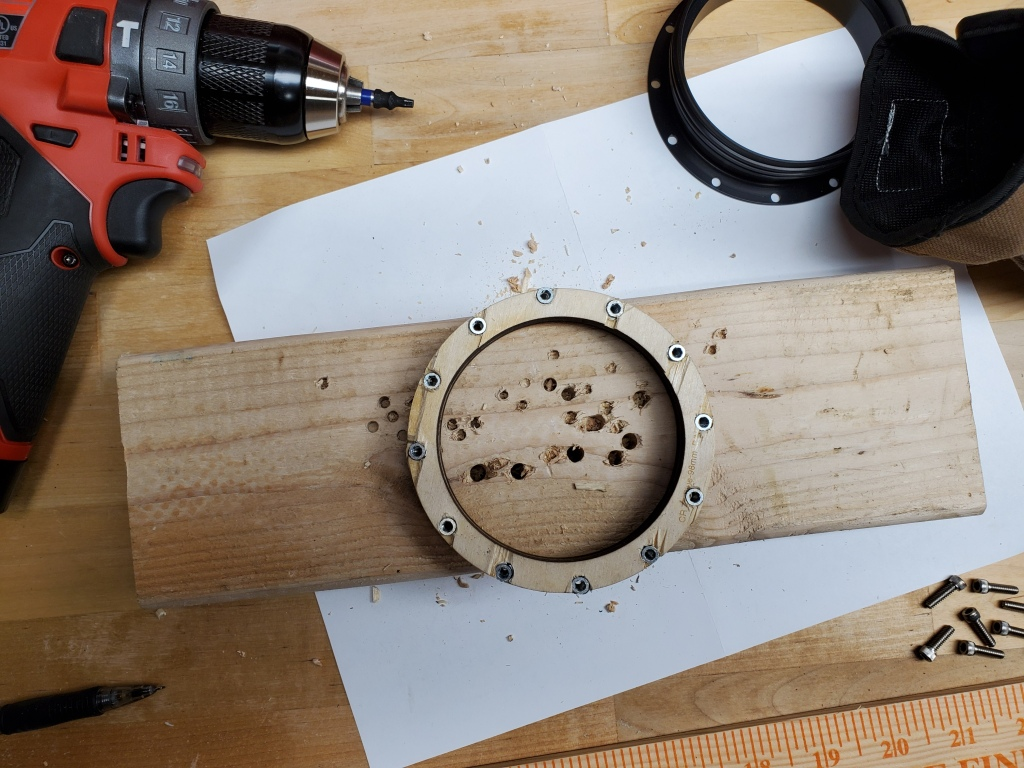 metal screws in wooden centering ring, on workbench with drill nearby
