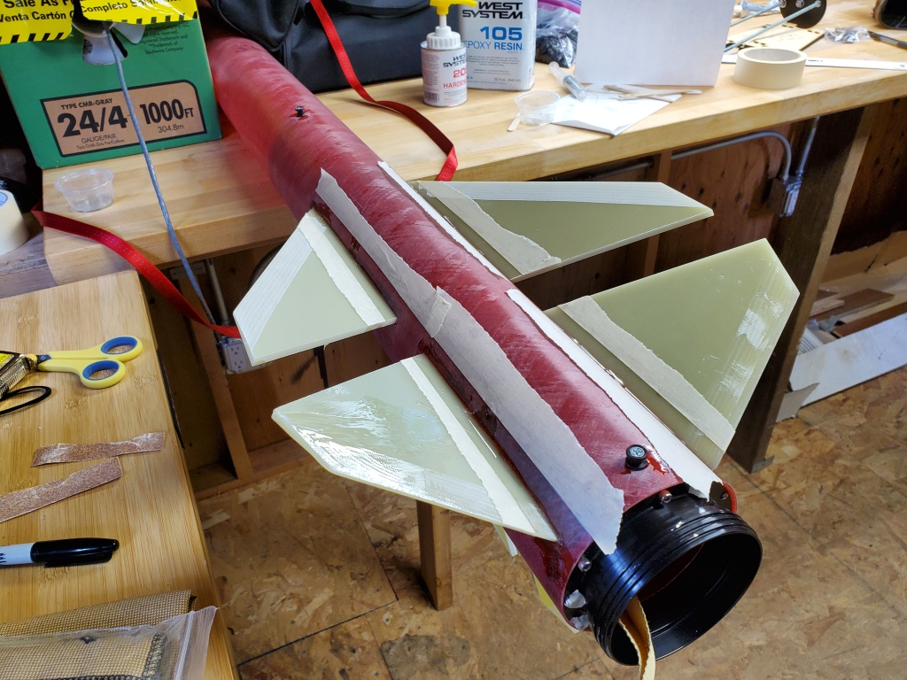 fiberglass rocket and fins on workbench, with masking tape creating lines