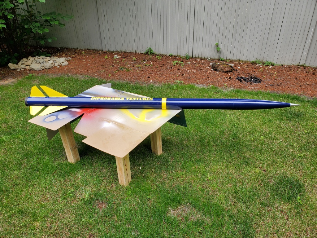 long blue rocket on wooden test stand, on grass - side view