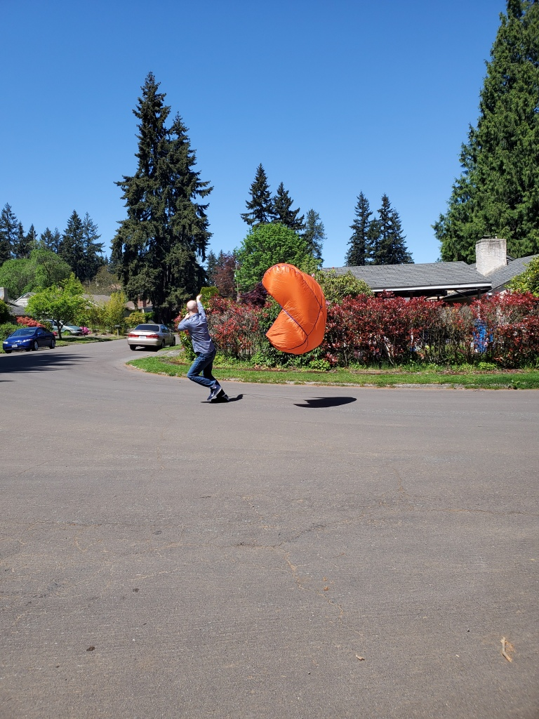 person running in street, pulling orange parachute behind in the air