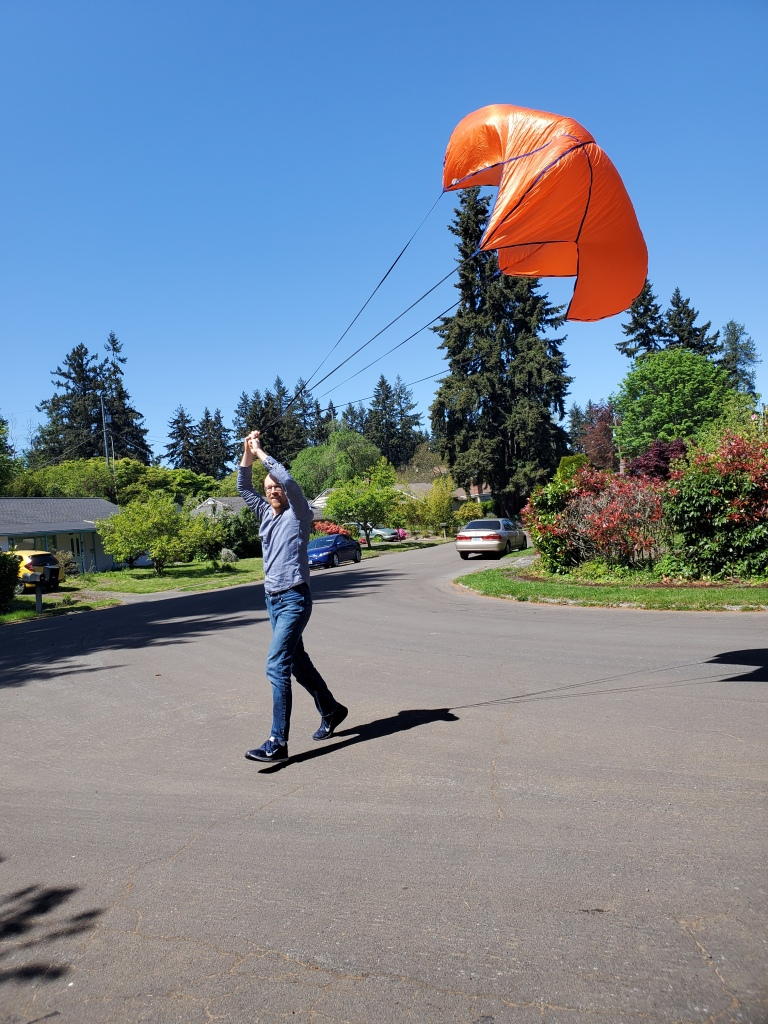 person in street, holding open orange parachute above head