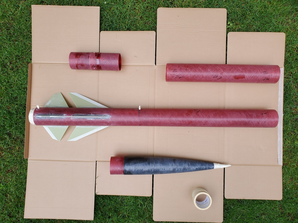 rocket disassembled on cardboard and grass, no paint or primer