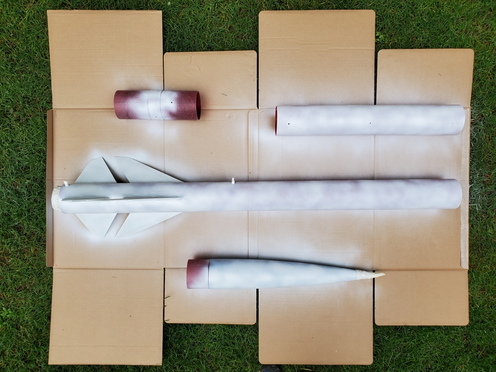rocket disassembled on cardboard and grass, white primer applied