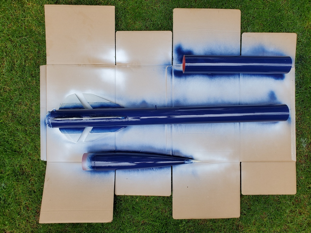 rocket disassembled on cardboard and grass, painted glossy navy blue