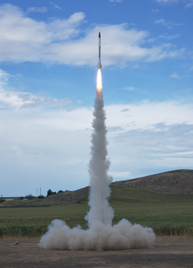 rocket launching into the blue sky, with fire and smoke below