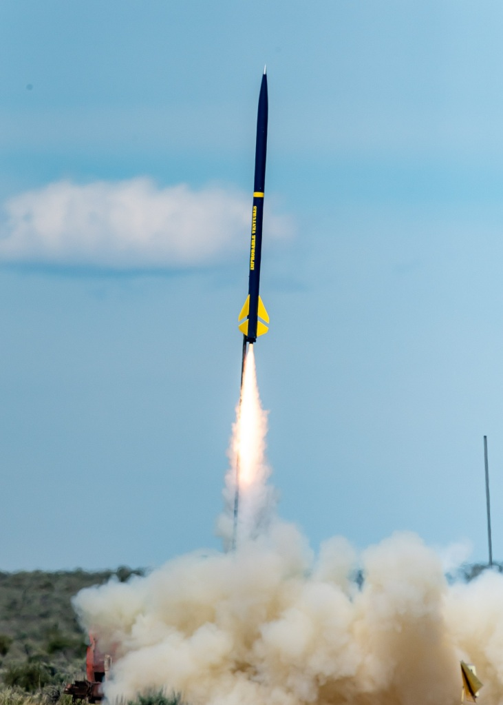 navy blue and yellow rocket in flight with cloud of smoke beneath it