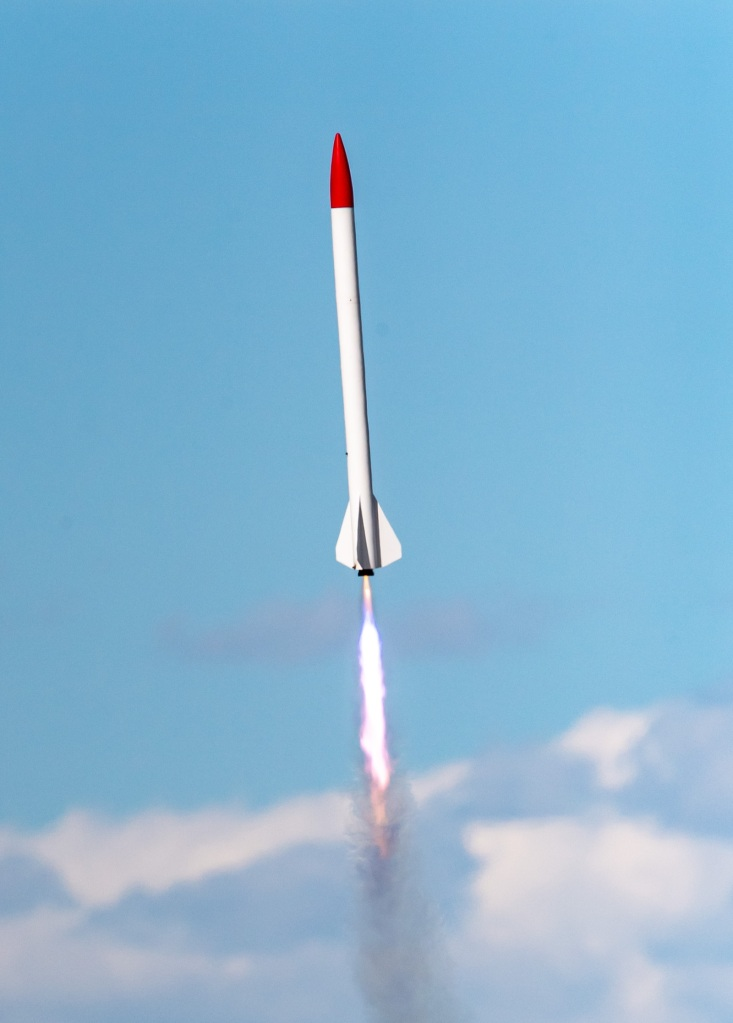 red and white rocket in flight