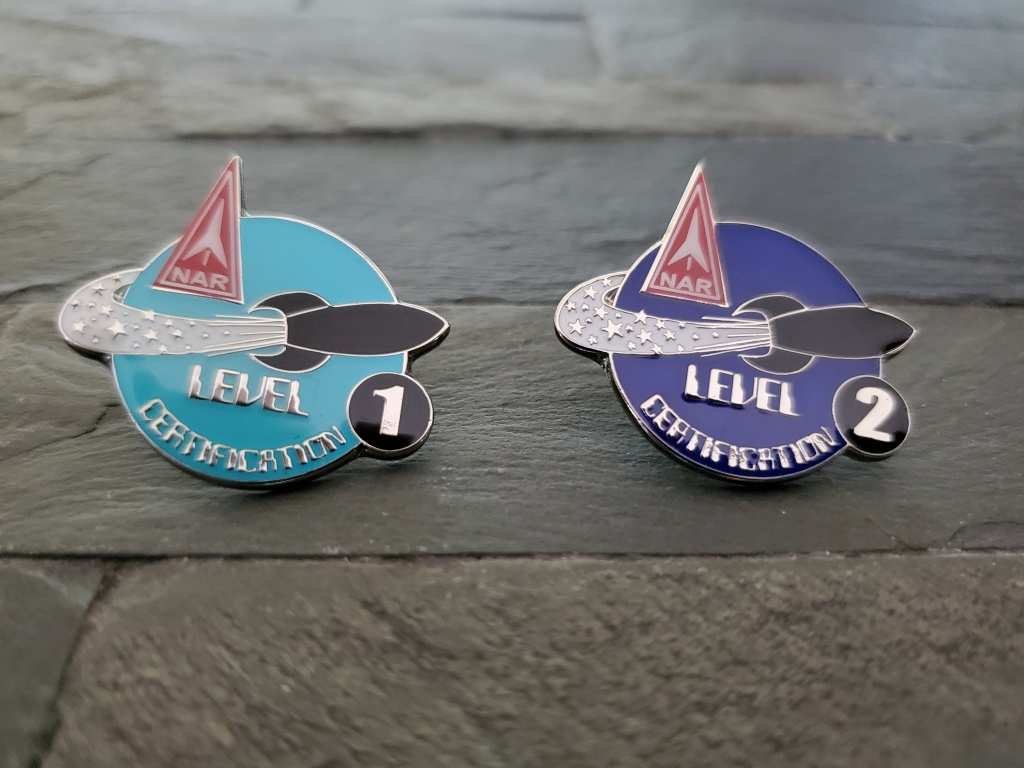 close up of metal badges that say level 1 and level 2 certification