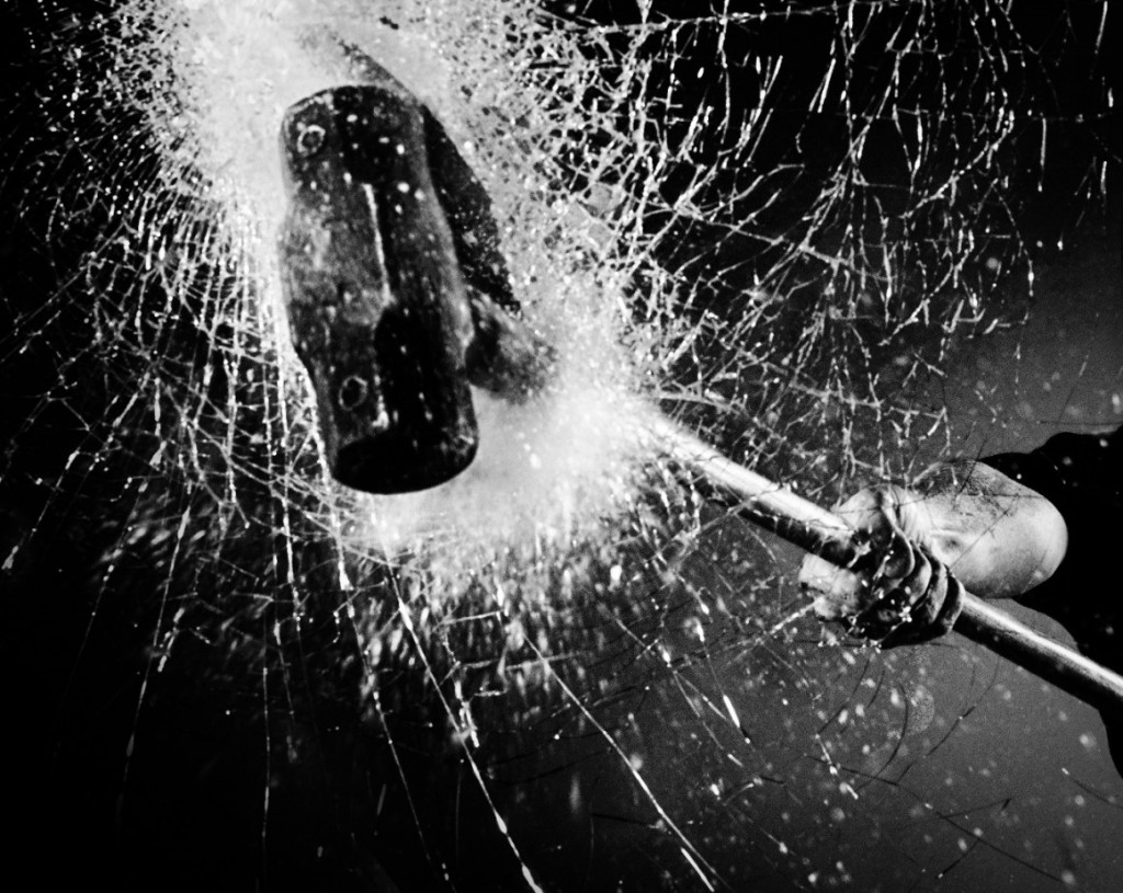 black and white photo of sledgehammer breaking glass