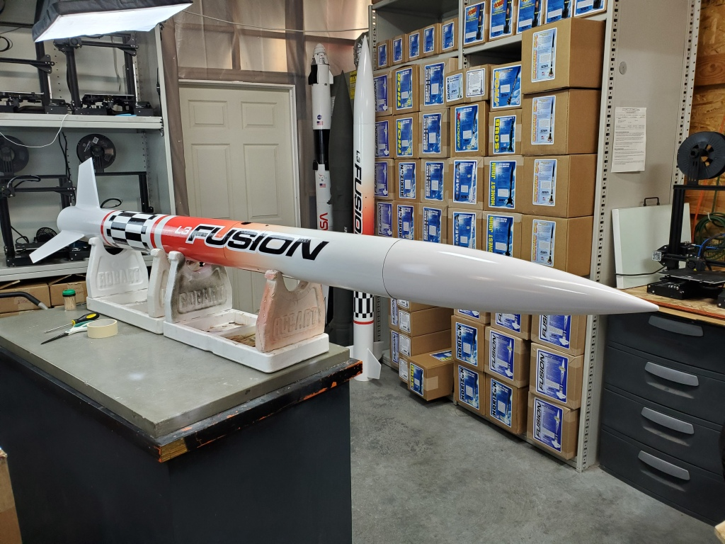 "Large white rocket with ""Fusion"" decal, on display on a table"