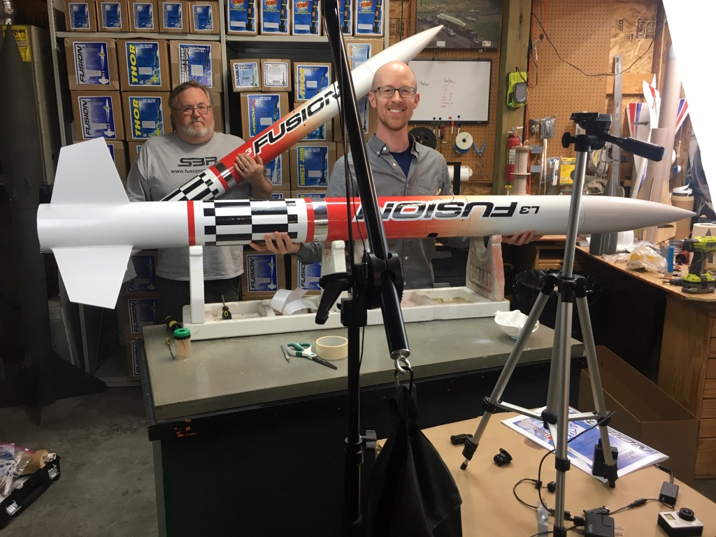 Two men standing in a workshop, holding large white rockets