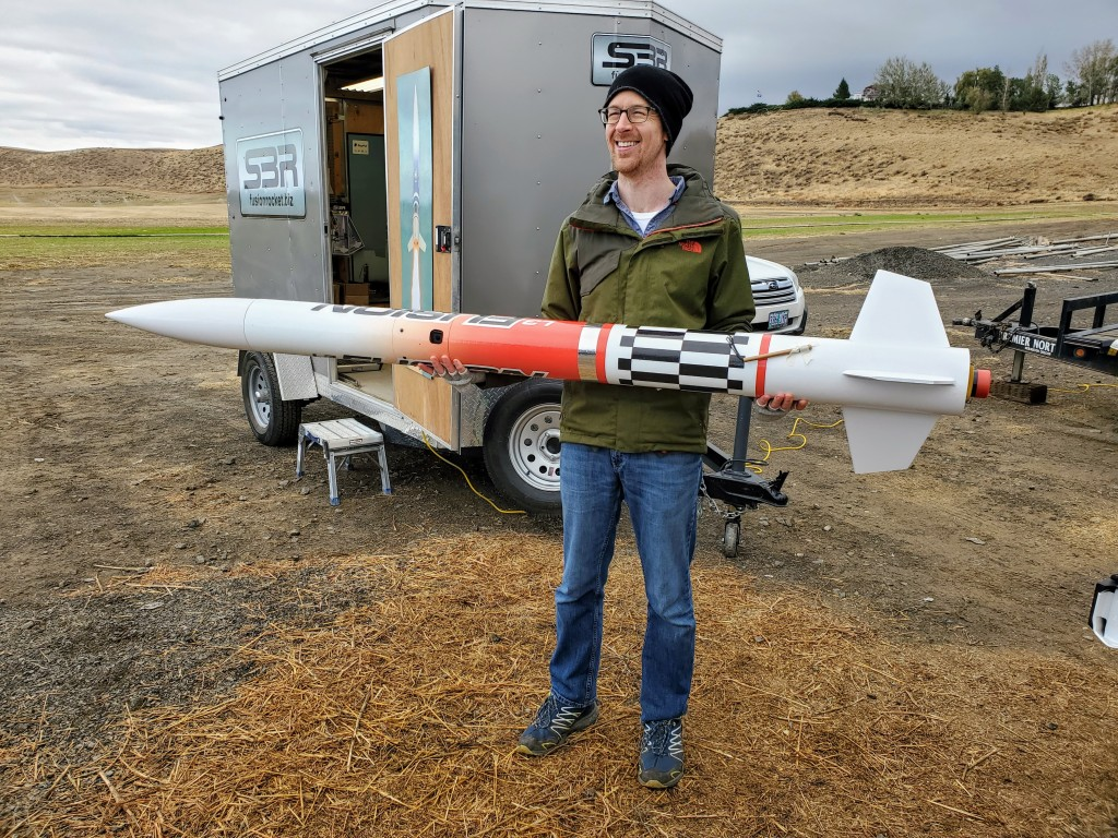 man standing in front of small trailer holding large red and white rocket