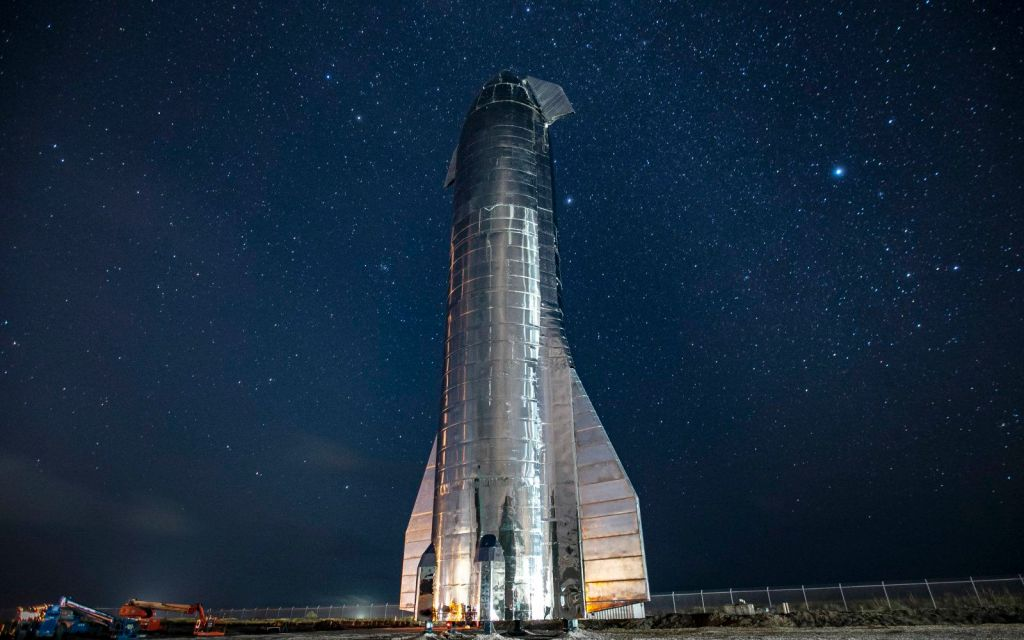 Starship SN-8 silver metallic rocket standing vertically against starry blue night sky