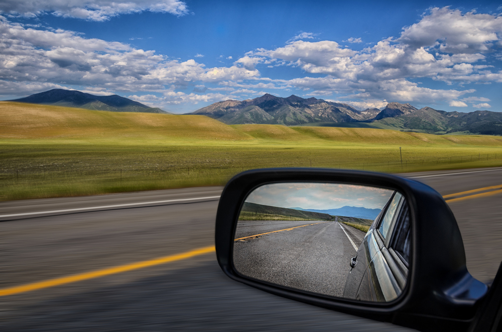 Rearview mirror in a car with road and mountains