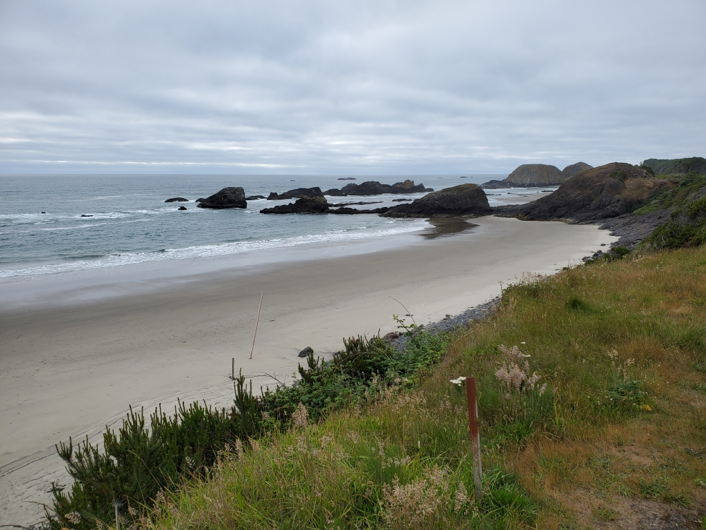 coastline with beach and large rocks in the distance on a cloudy day