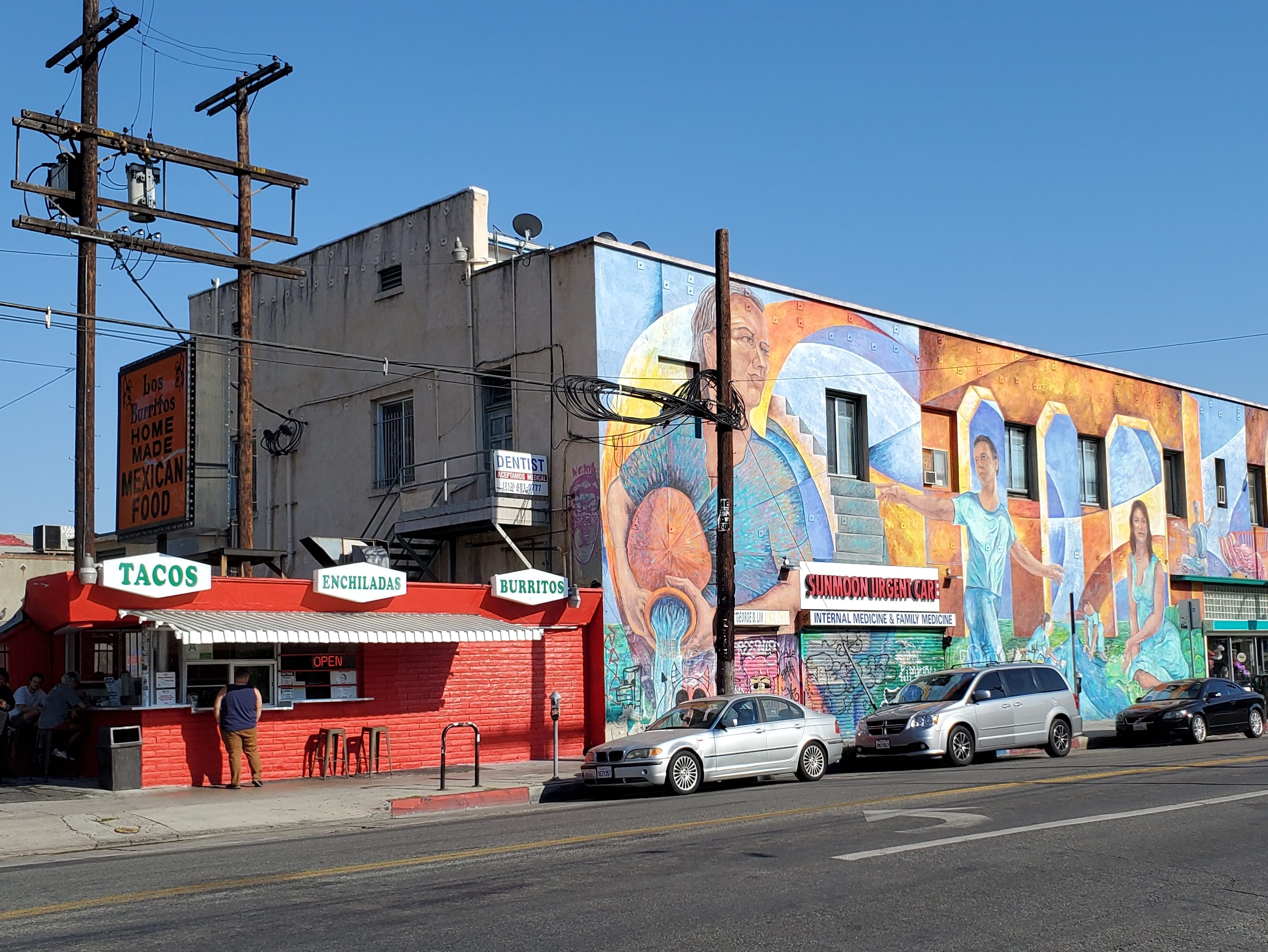 mexican food restaurant and painted mural on building with city street in foreground
