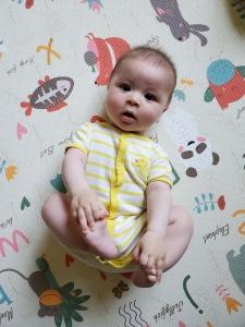 baby on play mat looking curiously at camera